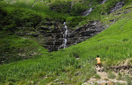 Boy running through sunny field toward waterfall