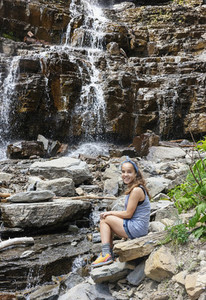 Portrait happy girl sitting below waterfall