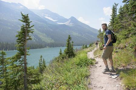 Portrait happy man hiking on sunny lakeside trail