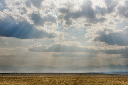 Sunbeams shining through clouds onto Montana countryside