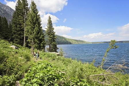 Hikers along sunny idyllic Jenny Lake