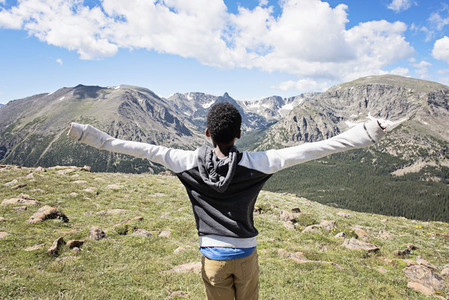 Carefree boy with arms outstretched enjoying sunny mountain view