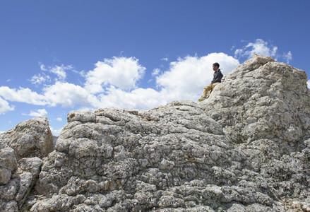 Boy sitting atop sunny rocks