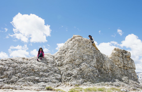 Boy and girl climbing large rock