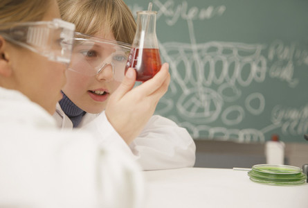 Junior high school students examining beaker of liquid in science class