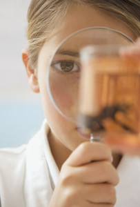 Close up curious junior school high girl with magnifying glass