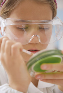 Close up junior high school girl in science goggles with petri dish