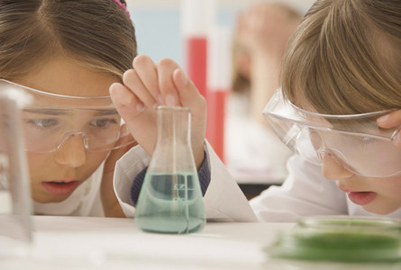 Curious junior high school girl students examining liquid in science beaker