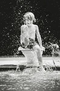 Portrait playful boy splashing water at swimming pool
