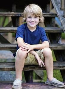 Portrait smiling boy sitting on wooden steps