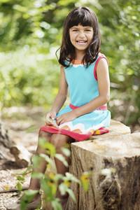 Portrait happy girl sitting on tree stump