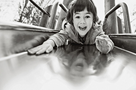 Portrait playful girl on playground slide