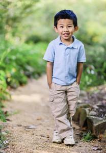 Portrait cute boy standing on footpath