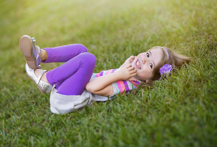 Portrait happy girl laying in grass