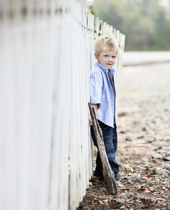 Portrait boy leaning on fence