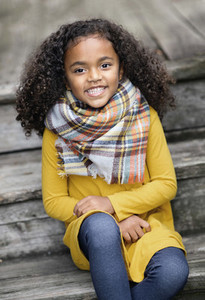 Portrait happy girl in plaid scarf on wooden steps