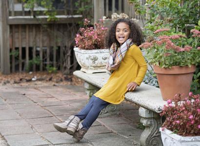Portrait happy girl on garden bench