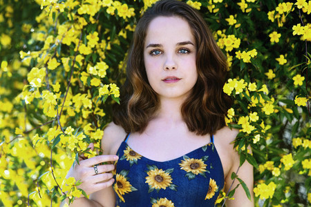 Portrait teenage girl surrounded by yellow flowers