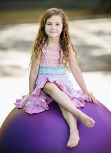Portrait cute girl in dress sitting on purple fitness ball