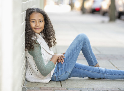 Portrait confident girl sitting on urban sidewalk