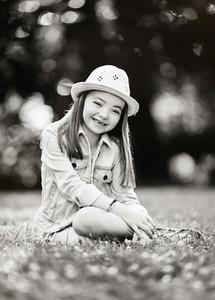 Portrait happy girl in hat sitting in grass