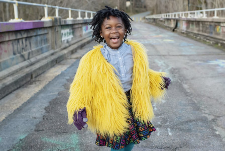 Portrait happy girl in yellow fuzzy jacket on bridge
