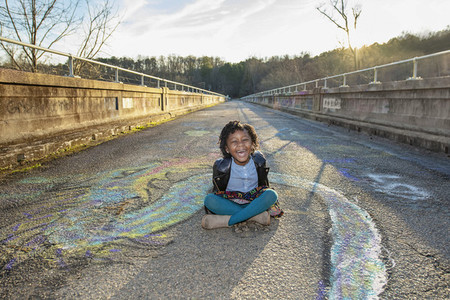 Portrait happy girl sitting among graffiti on sunny bridge