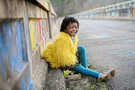 Portrait happy girl in yellow furry jacket on bridge