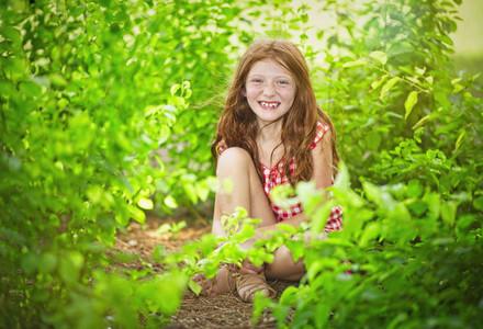 Portrait happy girl sitting in bushes