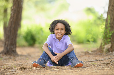 Portrait confident boy sitting in woods