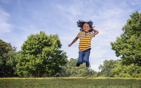 Portrait playful boy jumping in sunny field