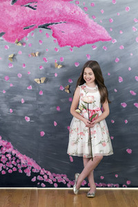 Portrait smiling girl in dress with flower against pink painted backdrop