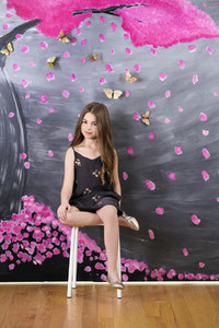 Portrait girl in dress sitting at wall painted with pink tree and butterflies