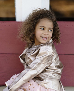Portrait smiling girl with curly hair looking over shoulder