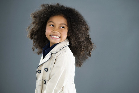 Portrait enthusiastic girl with curly black hair looking over shoulder