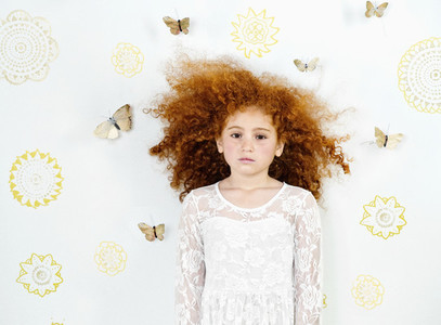 Portrait serious girl with curly red hair against butterfly backdrop