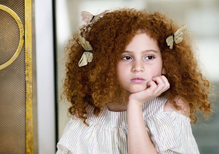 Portrait serious girl with butterflies in curly red hair looking away