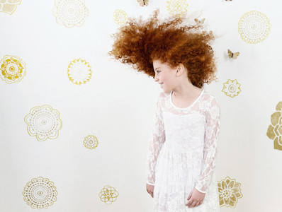 Portrait carefree girl with curly red hair against pattern backdrop