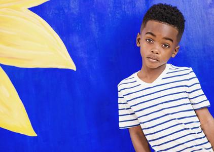 Portrait confident boy in striped shirt against vibrant blue wall