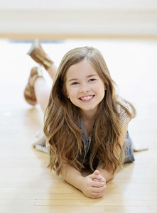Portrait carefree girl with long brown hair laying on hardwood floor