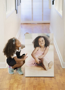 Girl looking at printed portrait of herself in corridor