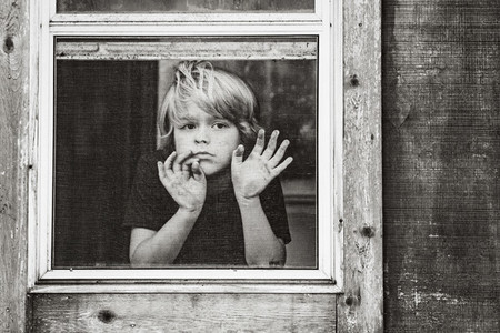 Portrait serious boy looking out window