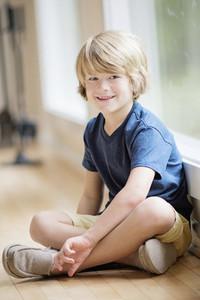 Portrait smiling blonde boy sitting at window