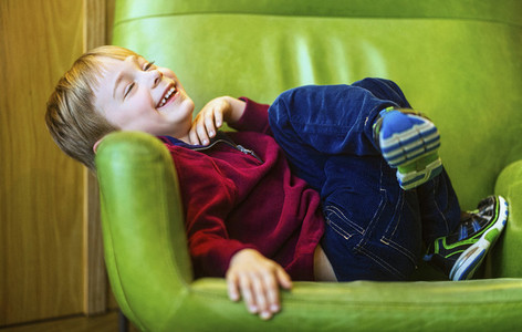 Portrait carefree boy laughing in green armchair