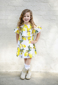 Portrait confident girl in lemon dress standing at white brick wall