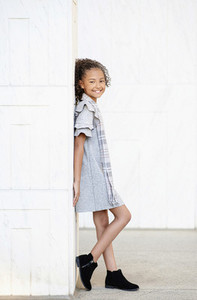 Portrait smiling confident girl in dress and booties standing at wall
