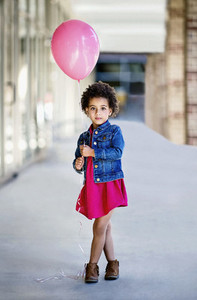 Portrait confident girl in denim jacket holding pink balloon