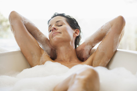 Sensual woman enjoying bubble bath