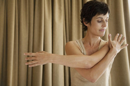 Serene woman stretching shoulder