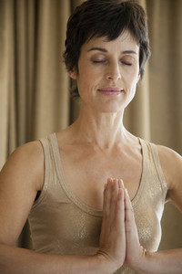 Serene woman meditating with hands clasped